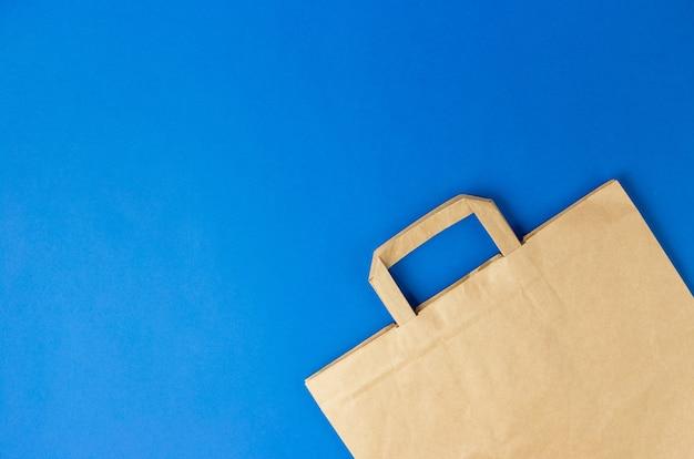 Ремесло коричневый бумажный мешок с ручками на синем фоне. плоский баннер, вид сверху, место для копирования, нулевые отходы, предметы без пластика. мокап эко-пакета, доставка или концепция онлайн-покупок