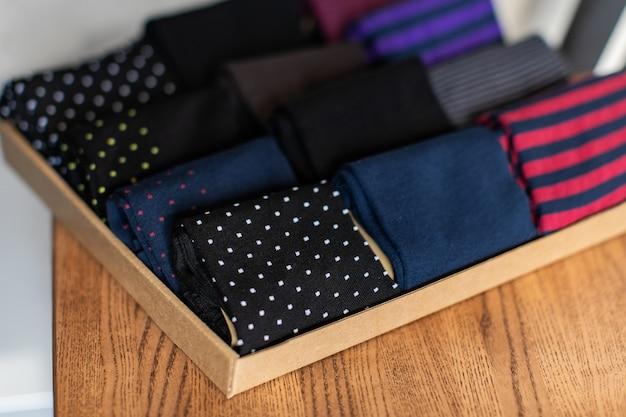 Craft картонная коробка с набором разноцветных мужских носков на деревянных поверхностях под солнечным светом