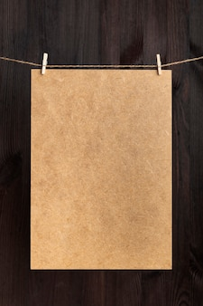 Craft cardboard hanging with clothespins on rope. place for your text. copy space, mockup. vertical frame