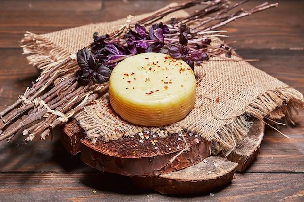 나무 판자에 있는 천에 풀 한 다발을 넣은 공예 치즈