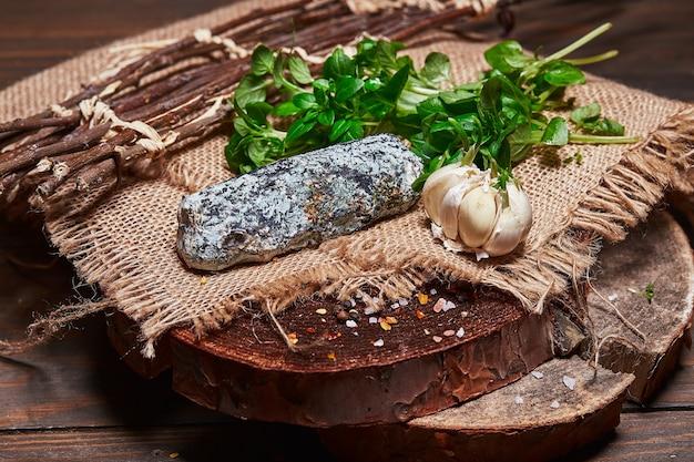 나무 판자에 있는 천에 허브와 마늘 정향을 넣은 수제 치즈