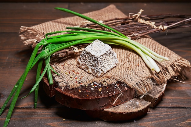木製のログハウスの黄麻布にネギとチーズを作る