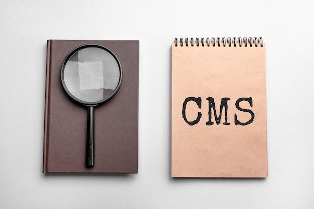 텍스트 cms로 색 메모장을 만드십시오. , 돋보기가있는 메모장. 비즈니스 개념