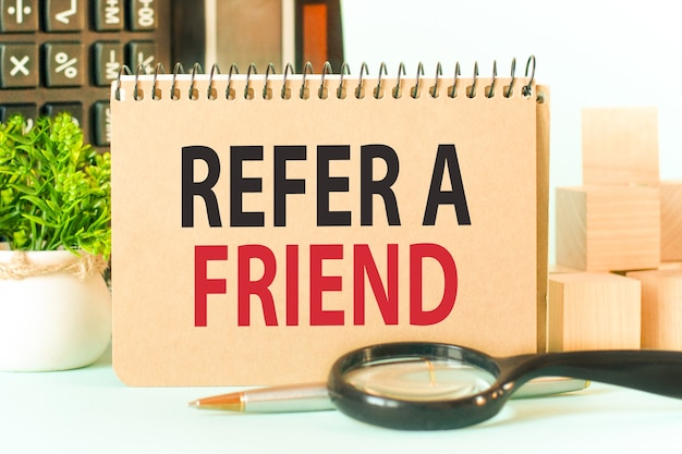 Refer a friend 텍스트가있는 색 메모장을 만듭니다. 계산기, 나무 블록, 돋보기, 녹색 꽃과 메모장.