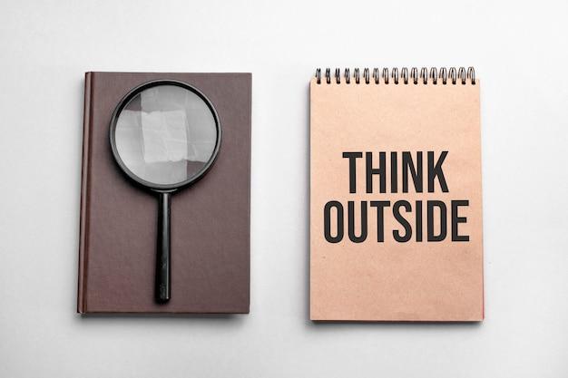 Создайте цветной блокнот с текстом think outside. блокнот с увеличительным стеклом
