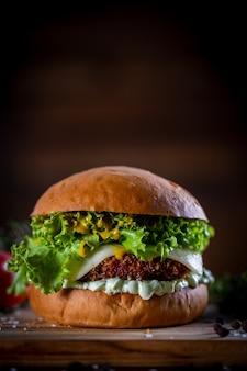 Приготовьте хрустящий куриный бургер с сыром, листьями салата, помидорами и соусом на деревянном фоне
