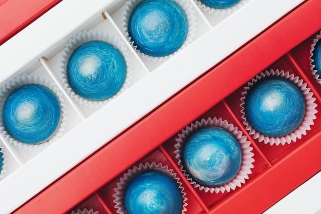 상자에 돔 모양의 다크 초콜릿 캔디를 만드세요. 무늬. 휴가를위한 달콤한 선물