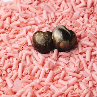 Нарисуйте конфеты из темного шоколада в форме двойного сердца на завитках из розового шоколада. сладкий подарок на день святого валентина