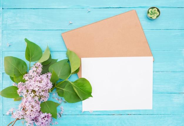 クラフト封筒、ホワイトペーパー、ビンテージターコイズブルーの木製の背景にライラック、グリーンキャンドルのブランチ