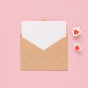 Ремесленный конверт, белая карточка чистого листа бумаги и сердечки деревянных зажимов на розовом фоне. место для текста. плоская планировка. вид сверху. с днем святого валентина.