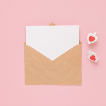 Craft envelope, blank paper white card and wooden clips hearts on a pink background. place for text. flat lay. top view. happy valentines day.