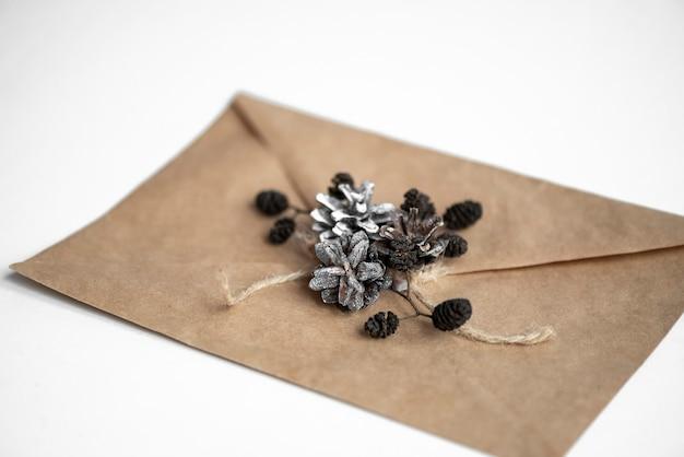 松ぼっくりで作られたクリスマスの装飾が施されたグリーティングカードのクラフト封筒