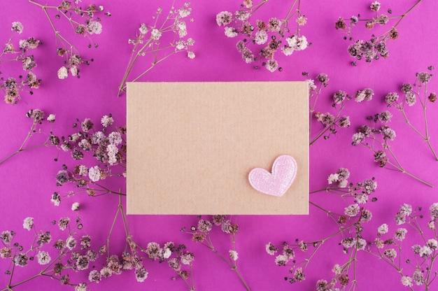 花とピンクの表面にクラフト封筒