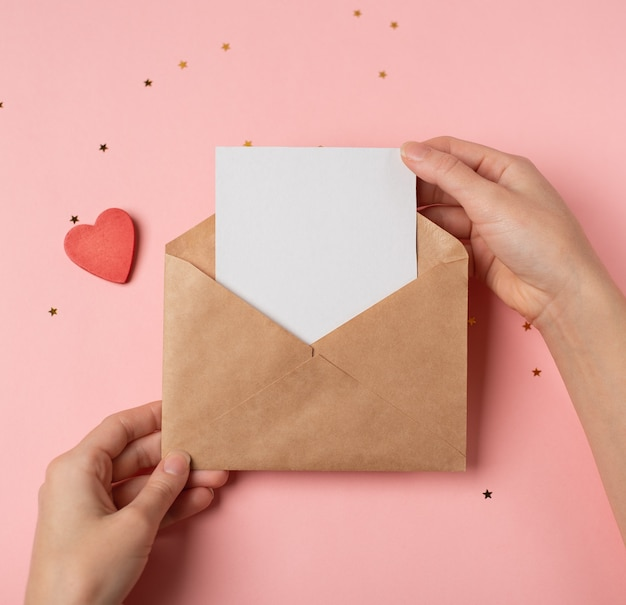 Craft envelope with a blank sheet in woman's hands on the pink background. flat lay, top view