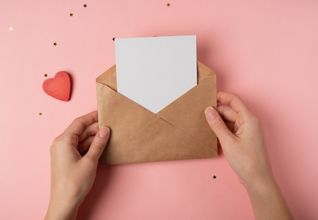 Craft envelope with a blank sheet in woman's hands on the pink background. top view. valentine's day concept.