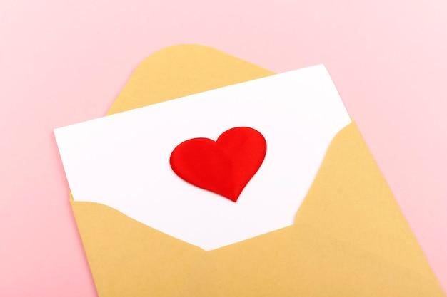 파스텔 핑크 배경에 흰색 카드에 붉은 마음으로 공예 봉투. 평면 평신도, 평면도. 발렌타인 데이 개념. 어머니의 날 개념.