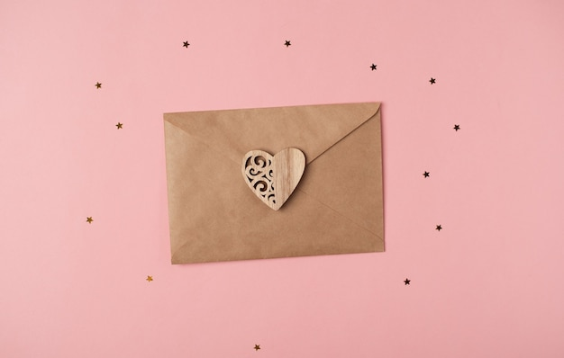 Craft envelope with wooden heart on it on the pink background with stars. romantic love letter for valentine's day concept. top view.