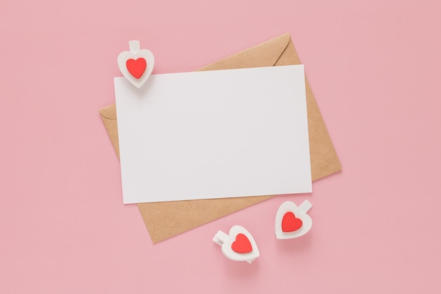 공예 봉투, 종이의 흰색 빈 시트와 분홍색 배경에 나무 클립 하트. 발렌타인 데이 개념.