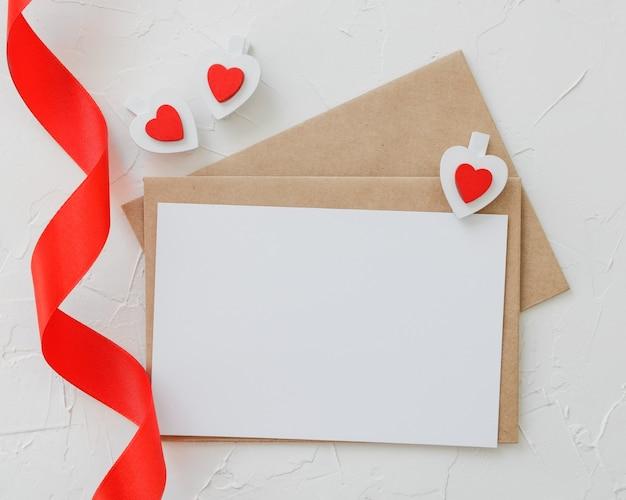 Ремесленные конверты, белый чистый лист бумаги, сердечки из деревянных зажимов и красная лента