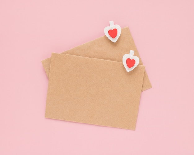 Craft envelopes and wooden clips hearts on a pink background. valentine's day concept.