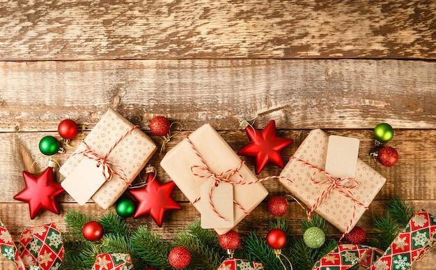 赤と白のロープで結ばれ、木製のテーブル、上面図にクリスマスの緑と赤の星とボールで飾られたクラフトギフトボックス
