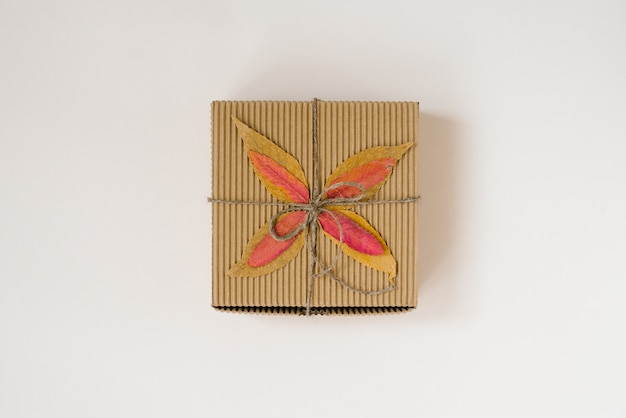 Craft gift box, tied with string with a bow and autumn fallen leaves on a beige background.