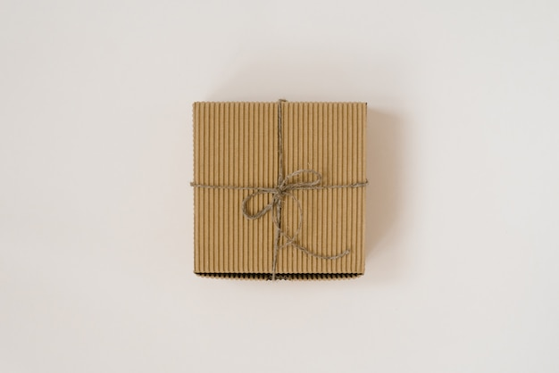 Подарочная коробка craft связанная с шпагатом с на бежевой предпосылкой. подарочная упаковка на день рождения.