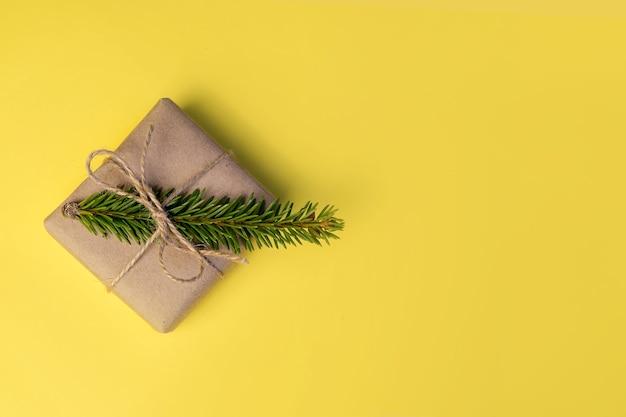 노란색 바탕에 크리스마스 트리 분기와 공예 선물 상자. 상단에서보기. 미니멀리즘.