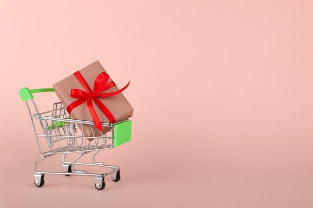 Ремесло подарочная коробка с красной лентой в мини-продуктовой тележке на розовом фоне