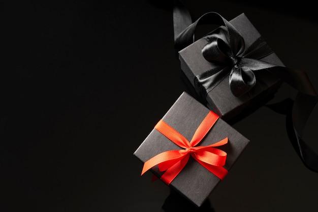 Изготовьте подарочные коробки с бантами на темном фоне. праздничный шаблон.