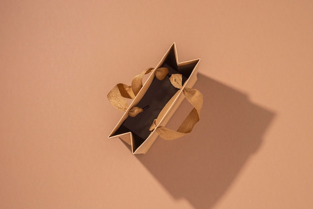 Craft gift packet with satin ribbon on brown background. top view, flat lay.