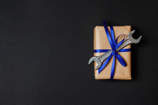 Craft gift with old tool on black paper background. fathers day concept. flat lay