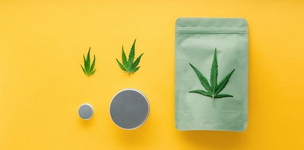 大麻の葉と金属の瓶でグリーンパッケージを作ります。さまざまなサイズの大麻パッケージ、雑草取引の合法化。薬局は黄色の背景に医療用マリファナの長いウェブバナーをドラッグします。