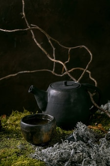 乾いた枝と葉のある苔の上に立っている手作りのセラミックティーポットケトルと熱い緑茶のわびさびカップを作ります。秋のネイチャーティーセレモニー。