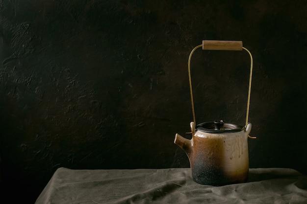 暗い部屋のリネンのテーブルクロスの上に立って茶道のための真鍮のハンドルが付いている手作りのセラミックティーポットケトルを作ります。