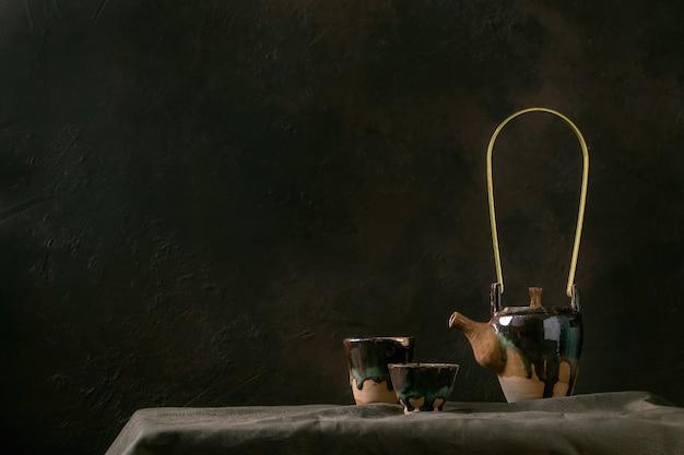 暗い部屋のリネンのテーブルクロスの上に立ってお茶の儀式のための熱い緑茶のカップで手作りのセラミックティーポットケトルを作ります。