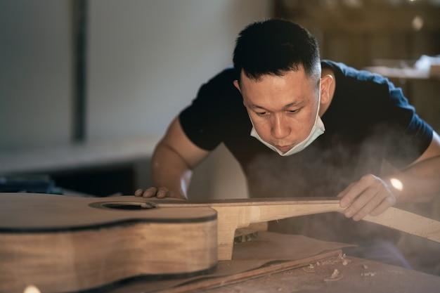 木製のテーブルでギターを作るクラフトマン、capenter作業コンセプト
