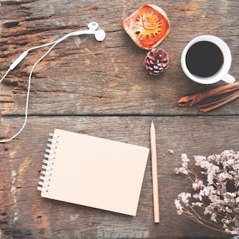 Craft notebook, pencil, cup of coffee and earphones on antique wooden table, view from above