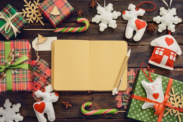 Craft notebook on the wooden table decorated for christmas with gifts sweets. top view