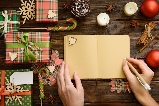 Craft notebook on the wooden table decorated for christmas with gifts and sweets
