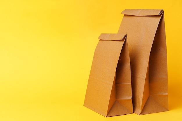 Ремесленные пакеты на фоне ярко-желтой бумаги крупным планом