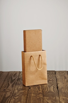 Craft paper bag with cardboard blank box inside presented on rustic wooden table, isolated on white background