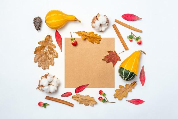 クラフト紙の空白のフレームと紅葉、綿、カボチャ、シナモンの背景。秋のモックアップ。秋の構成、秋のコンセプト。フラットレイ、トップビュー、コピースペース。