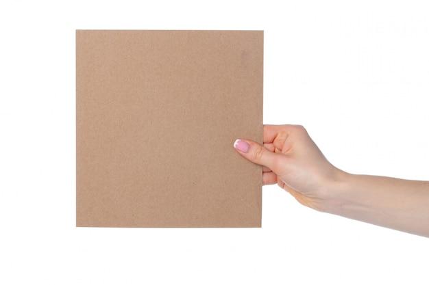 白で隔離される女性の手でクラフト紙カード