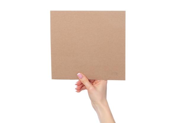 白い背景で隔離の手でクラフト紙カード