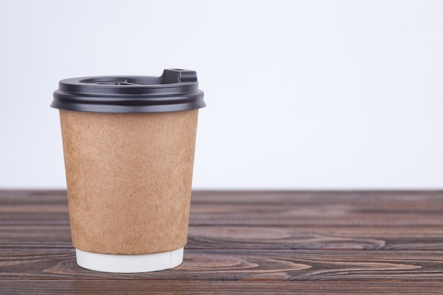 Craft paper coffee cups on a table near light wall background