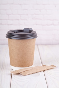 Craft paper coffee cups on a white table near light wall background