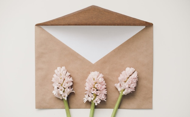 Craft paper envelop with white card and pink hyacinth flowers on white background. top view, flat lay, copy space.