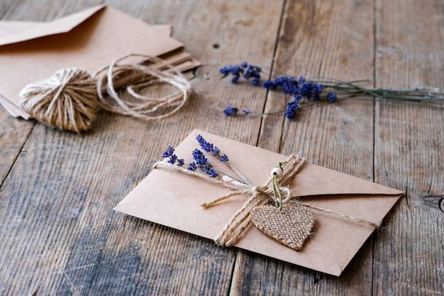 Конверт из крафт-бумаги лежит на деревянном столе, украшенном джутовой веревкой, сердечками и цветами лаванды. день святого валентина концепция нулевых отходов