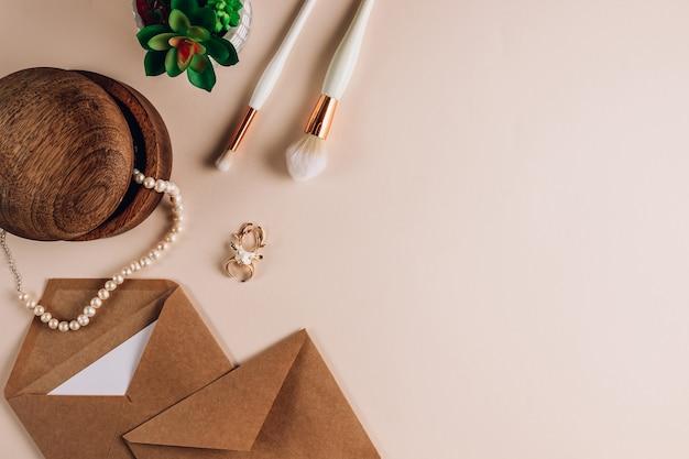 Конверт из крафт-бумаги с белым макетом для заметок с кистями для макияжа, очками и жемчужными бусинами на бежевом фоне. плоская планировка, вид сверху. приглашение, посылка и письмо